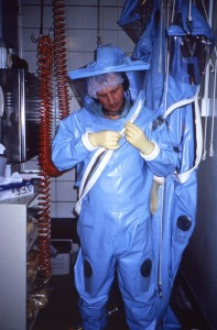 "This photograph depicted a Centers for Disease Control (CDC) laboratorian, as he was putting on an older-model positive-pressure suit before entering one of the CDC's earlier maximum containment, or Biosafety Laboratories (BSL), sometimes referred to as a ""suit lab"". Scientists working within a BSL must wear protective garments that are air-tight, thereby, protecting the technician from exposure to highly-infectious pathogenic organisms. Fresh, filtered air is supplied to the interior of the suit via overhead tubing. The positive-pressurization offers some added protection to exposure through a defect in the suit, for if the suit's patency is compromised, air would be forced out of the suit instead of being sucked into the suit."