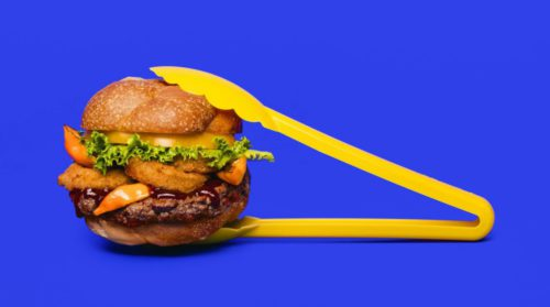 a cheese burger held by bright yellow tongs on a vivid blue background